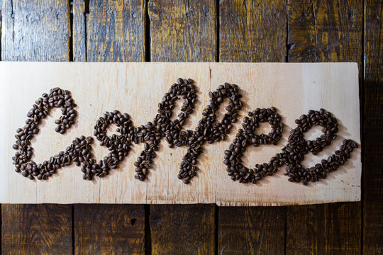 Coffee written on a slab of wood, in coffee beans