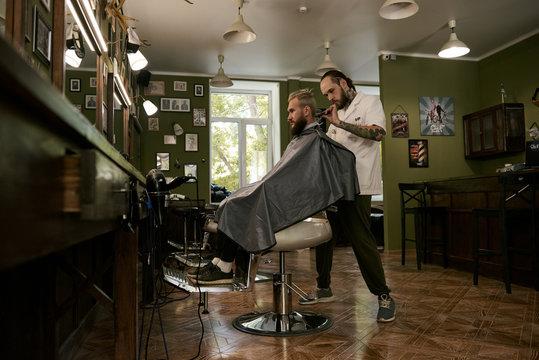 Barber giving haircut in salon
