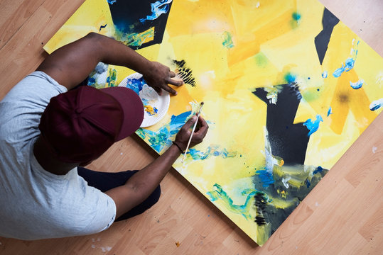 Artist painting abstract canvas with paintbrush.