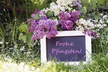 """Tafel mit Text""""Frohe Pfingsten"""" mit Flieder und Gänseblümchen im Garten"""