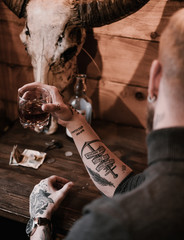 Close up of black style tattoo on anonymous man drinking whiskey