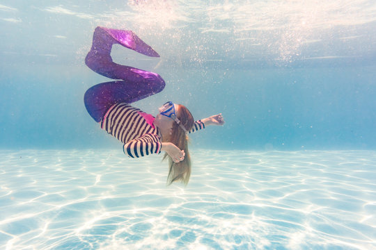 Girl on family vacation spins gracefully in swimming pool wearing mermaid costume