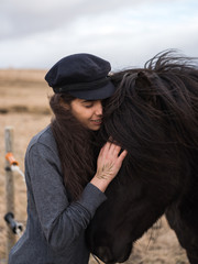 Young woman patting Icelandic horse