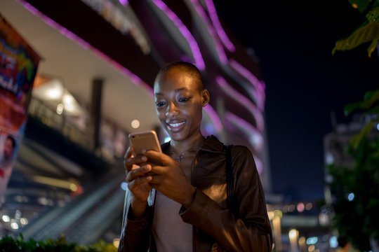 Night portrait of a woman smiling at her phone