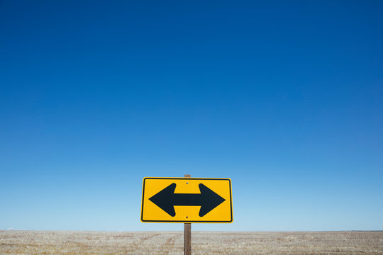 Arrow road sign, rural farmland in background