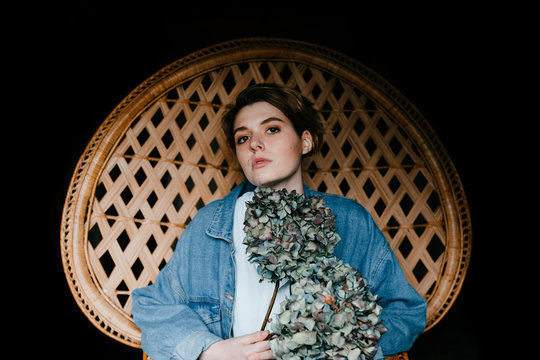 portrait of a beautiful androgynous teen woman sitting in a wicker chair holding some dry hydrangeas