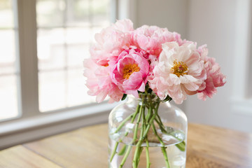 bouquet of pink peonies in a glass vase in a light filled room Fotobehang