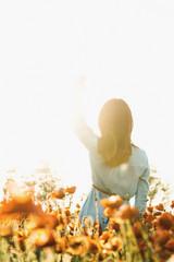 Romantic woman waving to the sun in flower meadow.