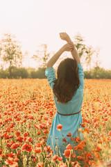 Rear view of romantic woman in poppy flower field.