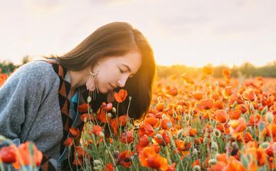 Romantic girl smelling a poppy flower in field.