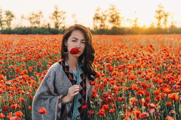 Pretty young woman with red poppy in flower meadow.