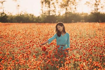 Romantic girl enjoying flower meadow.