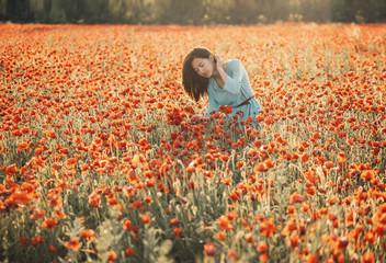 Romantic young woman walking in flower field.