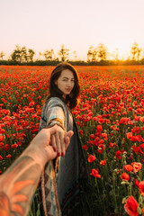 Woman leading a man in poppy meadow at summer sunset.