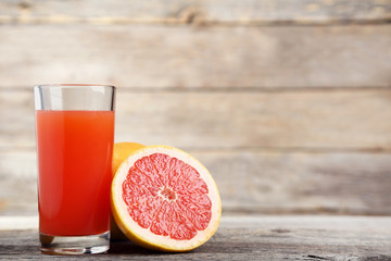 Wall Mural - Ripe grapefruits and glass of juice on grey wooden table
