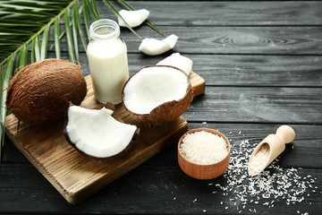 Wall Mural - Coconut milk in bottle with flakes and palm leafs on wooden table