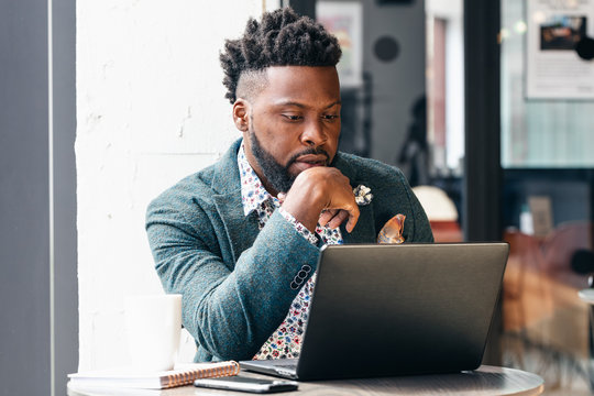 Businessman with chin on hand in front of laptop