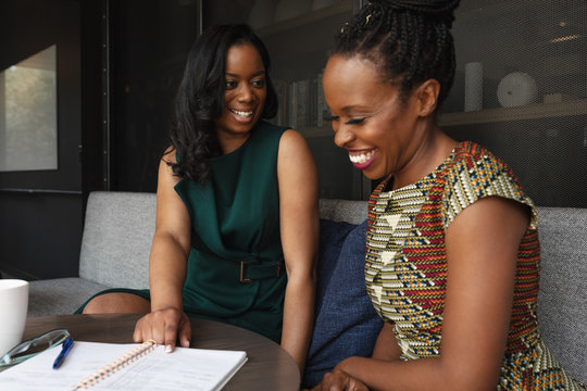 Two business woman laugh and look at notes