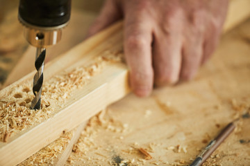 Fototapeta Extreme closeup of unrecognizable carpenter drilling wood while working in joinery, copy space obraz