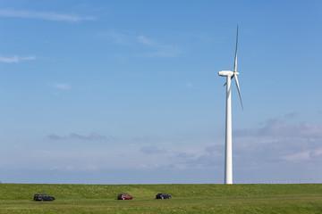 Dutch wind turbine near dike with parked cars