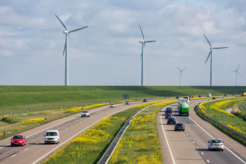 Dutch motorway near Lelystad with wind turbines and blooming rapeseed