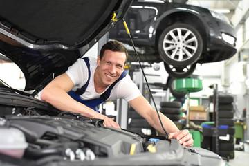 Portrait fröhlicher Automechaniker in der Werkstatt - Beruf Monteur Reparatur Fahrzeuge // car mechanic in a workshop - engine repair and diagnosis on a vehicle