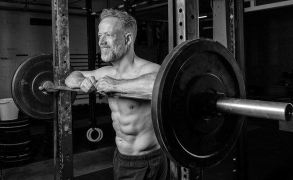 Älterer durchtrainierter Mann in den Fünfzigern beim Krafttraining. Der attraktive grauhaarige Sportler posiert lächelnd an der Langhantel. Training mit Gewichten.