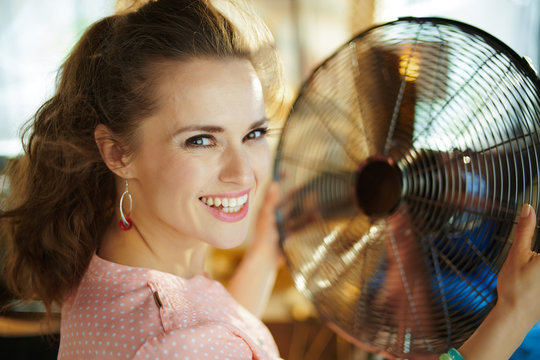 smiling housewife enjoying breeze air in front of working fan