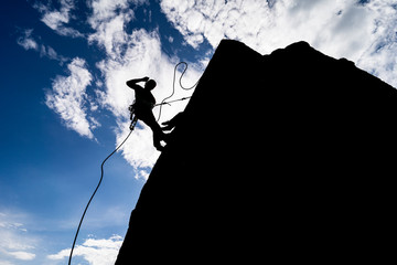 A dramatic silhouette of a climber rappeling down a rock wall. Rock climber with a rope abseil...