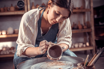 Fototapeta Stylish artisan making pottery, sculptor from wet clay on wheel. Craft manufacture. obraz