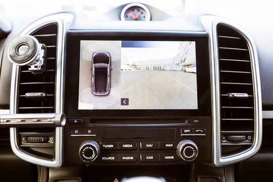 Display in interior of luxury car shows working of front camera in surround 360 degrees view assist system. Image display on the head unit. Multimedia in the car.