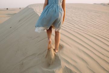 Girl walking on a sand dune in the desert in Dubai