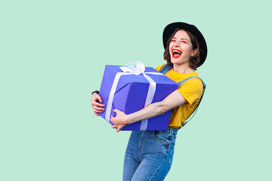 Satisfied happy beautiful young girl in hipster wear in denim overalls and black hat standing and holding big heavy gift box with toothy smile and laughing, open mouth. Studio shot, green background