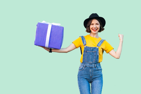 Happy attractive young girl in hipster wear in denim overalls and black hat standing and holding big heavy gift box with toothy smile, show strong arm, looking at camera. Studio shot, green background