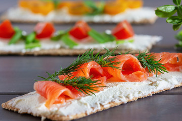 Crispbread with soft cheese, trout and dill, close-up. Easy summer snack. Light picture.