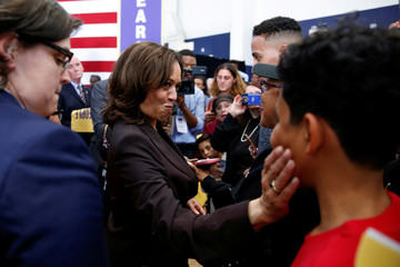 U.S. Senator Kamala Harris squeezes the cheeks of a young man after she had him shake her hand instead of making a high-five while greeting supporters following her first organizing event in Los Angeles as she campaigns in the 2020 Democratic presidential