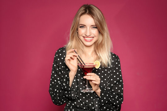 Beautiful young woman with glass of martini cocktail on color background
