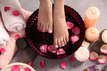 Wall Murals Pedicure Woman soaking her feet in bowl with water and rose petals on floor, top view. Spa treatment