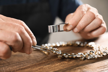Male jeweler evaluating necklace at table in workshop, closeup