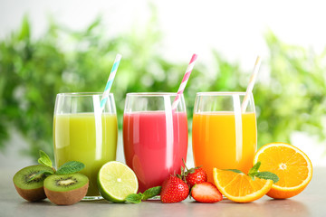 Glasses of different juices with straws and fresh fruits on table against blurred background Fototapete