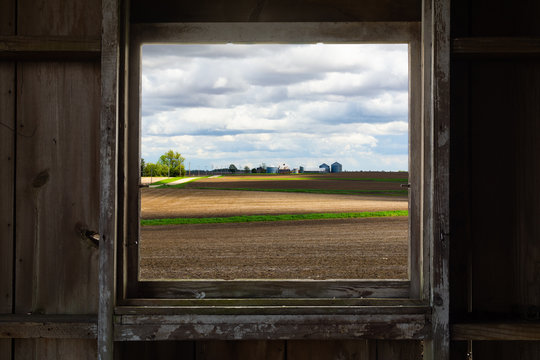Looking through the old barn window with a view of the open farmland. This morning in Malden, Illinois