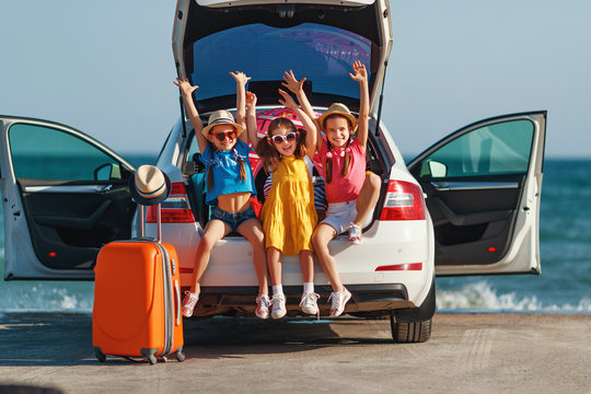 happy children girls friends sisters on the car ride to summer trip.