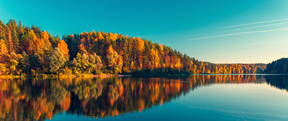 Silence at the forest lake at sunset, with reflection of sky and forest on a water smooth surface, Russia, Mari El