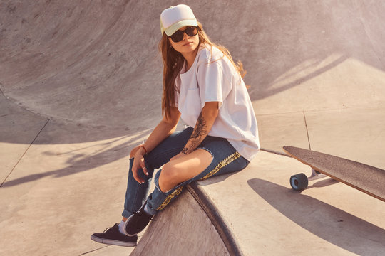 Beautiful young woman in sunglacces and cap is sitting at skatepark on the ramp with her longboard.