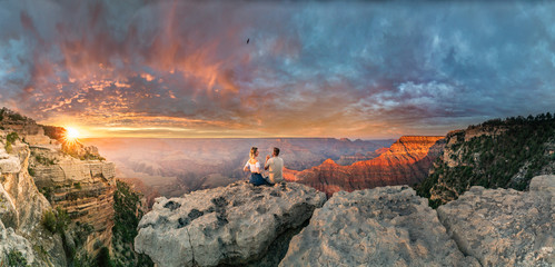 Man and woman sit on the edge of rim talking about future and watching the Grand Canyon sunset while bird in the sky