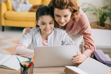 happy mother embracing smiling daughter doing schoolwork at home