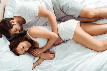 top view of handsome man and attractive woman sleeping in bedroom