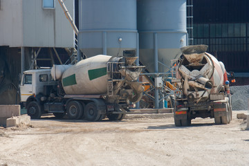 Two large cement truck trucks brought cement to the industrial area of the plant in special containers.
