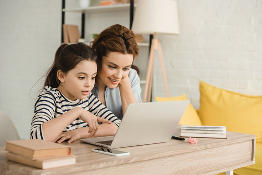 surprised mother and daughter using laptop while doing homework together