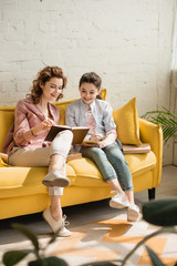 cheerful mother and daughter sitting on yellow sofa and reading book together